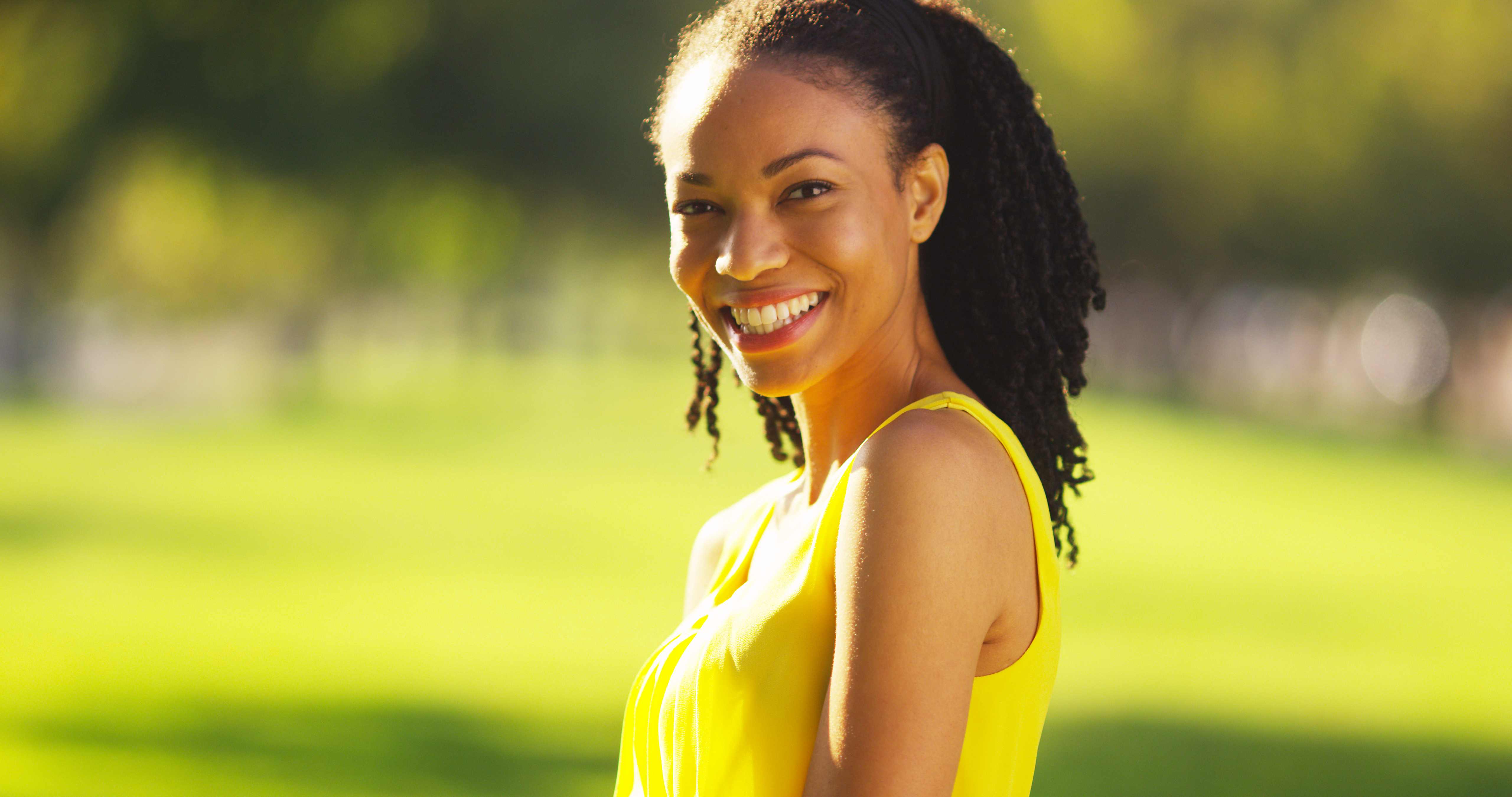 Black woman smiling in a field